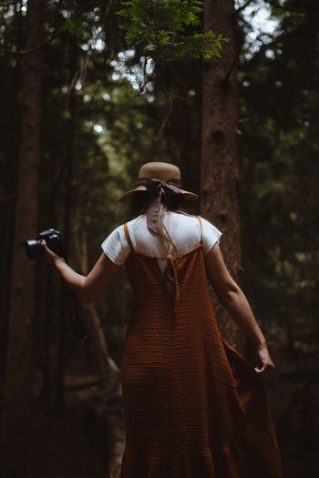 Rear view of woman holding camera while standing in woodland