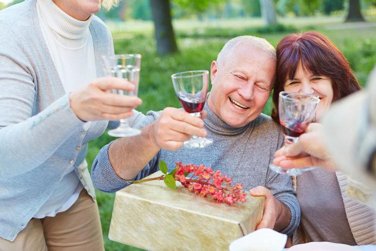 Smiling Friends Having Wine In Garden