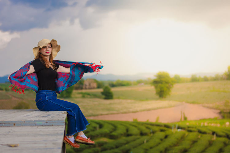 Woman with arms raised on field against sky in the choui fong tea plantation  thailand