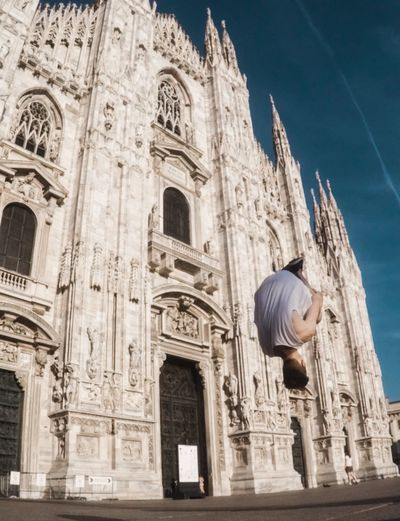 Low Angle View Of Man Jumping Against Milan Cathedral