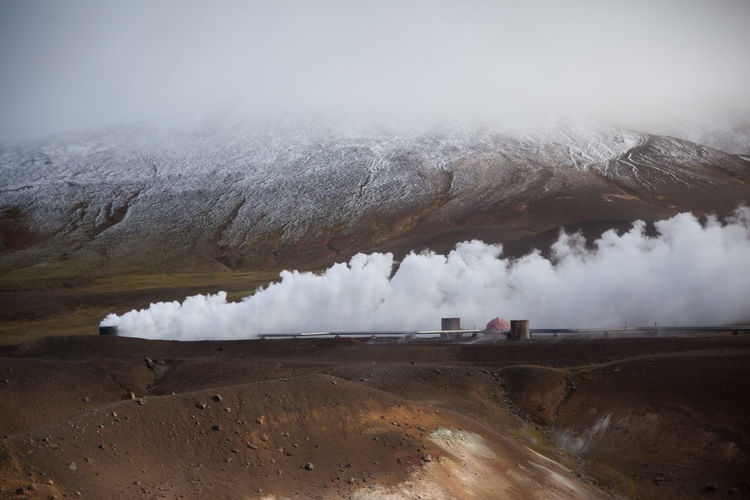 Smoke emitting from industrial site against snow covered mountain