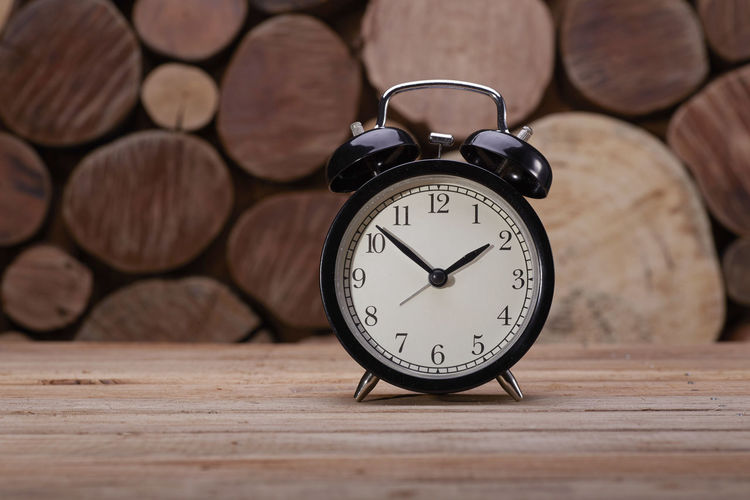 The Classic Black Alarm clock over wooden background Clock Time Wood - Material Number Table Alarm Clock Close-up Shape Still Life Indoors  No People Circle Geometric Shape Clock Face Focus On Foreground Accuracy Pattern Wood Minute Hand