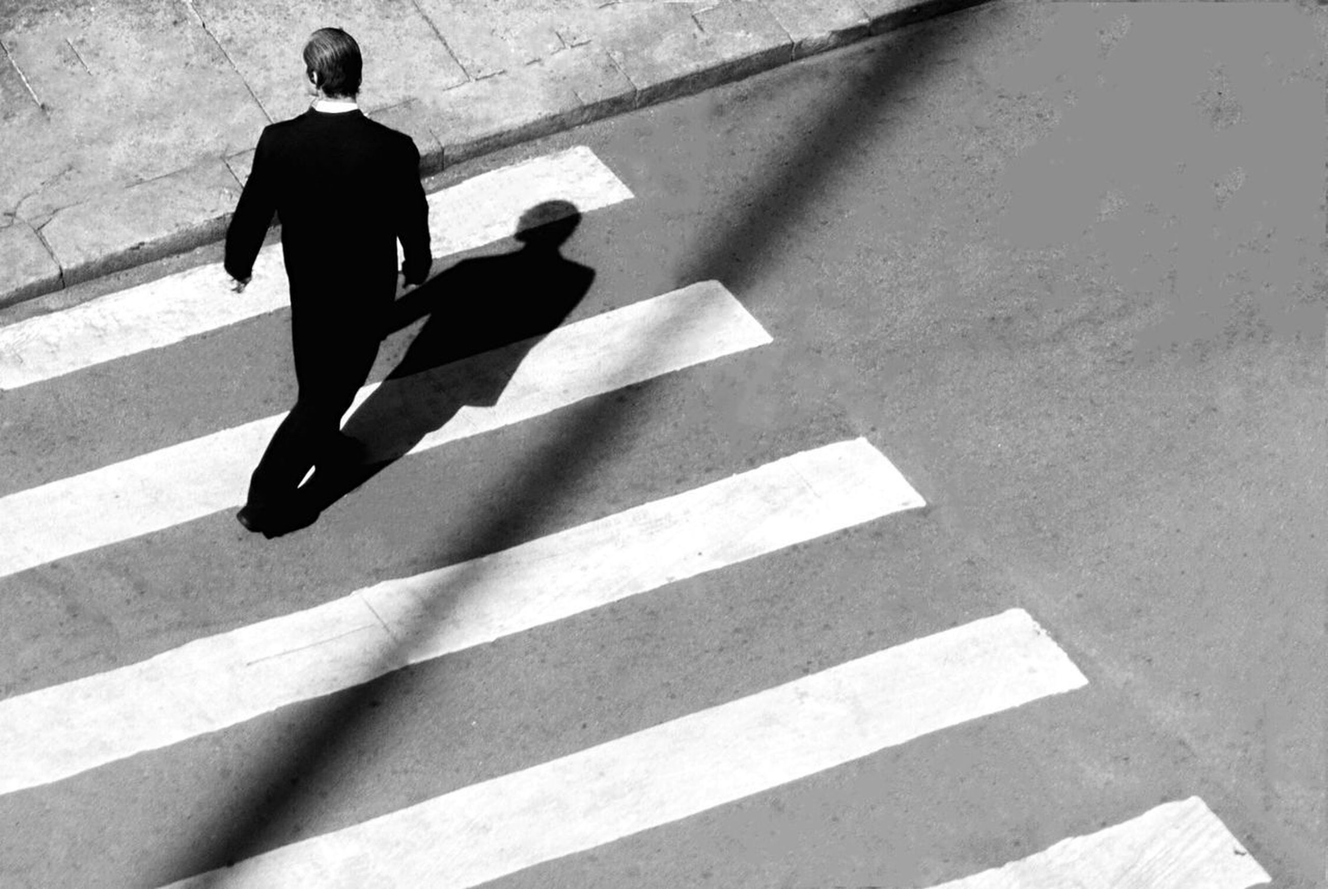 shadow, real people, high angle view, sunlight, men, city, road, street, lifestyles, day, people, walking, sign, marking, rear view, road marking, architecture, transportation, nature, outdoors