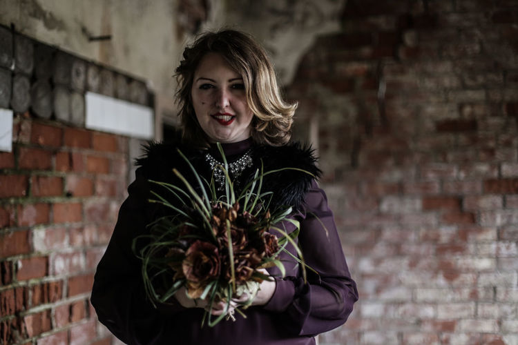 Portrait Of Young Woman Holding Dried Flowers Against Wall