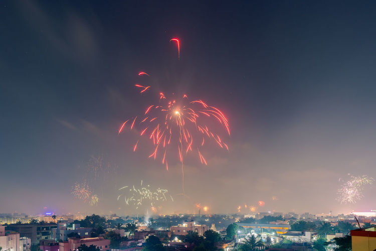 Low angle view of fireworks in city against sky at night