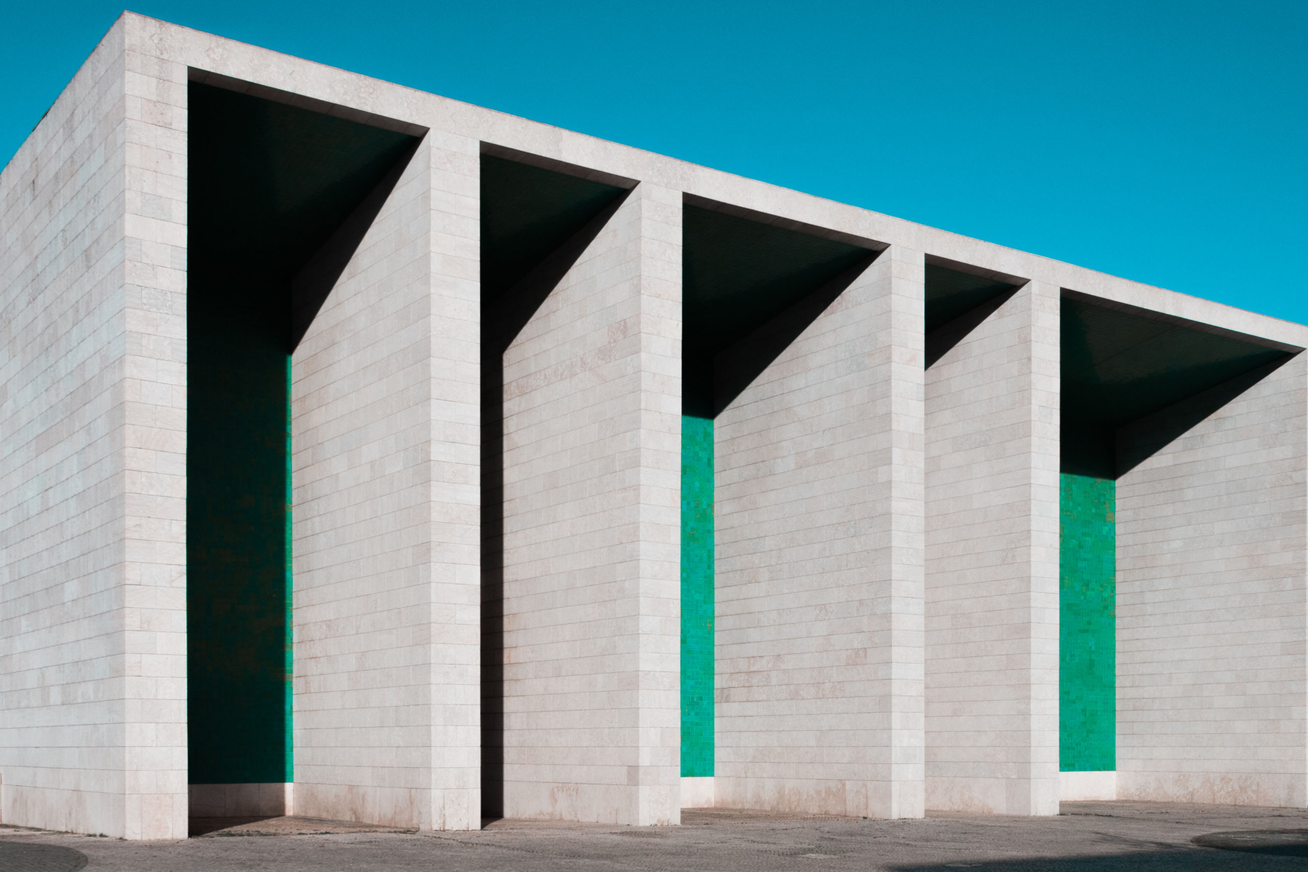 architecture, built structure, no people, building exterior, sky, blue, clear sky, low angle view, day, nature, outdoors, green color, side by side, sunlight, pattern, in a row, design, triangle shape, shape, art and craft, concrete