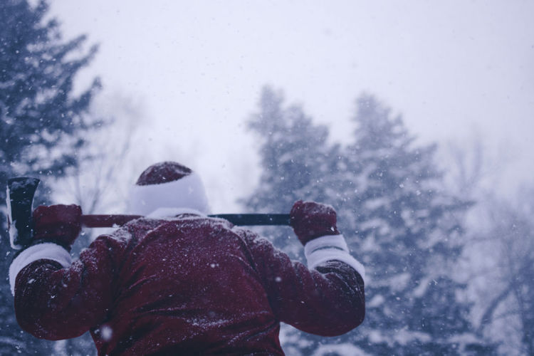 Rear view of mid adult man in santa costume holding axe while standing in forest during snowfall