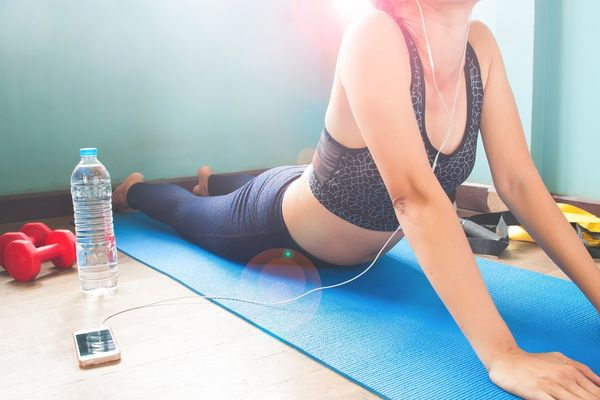 Woman in sport clothing doing yoga at home and listening music from mobile device Adult Bottle Day Drinking Water Exercising Gym Health Club Healthy Lifestyle Indoors  Leisure Activity Lifestyles Mobile One Person People Phone Real People Sports Clothing Water Water Bottle  Young Adult Young Women