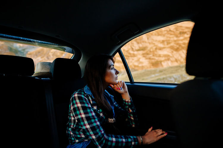 Side view of woman sitting in car
