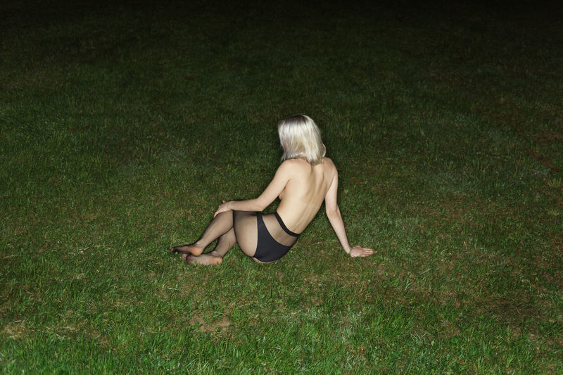 Rear view of topless young woman sitting on grassy field at night