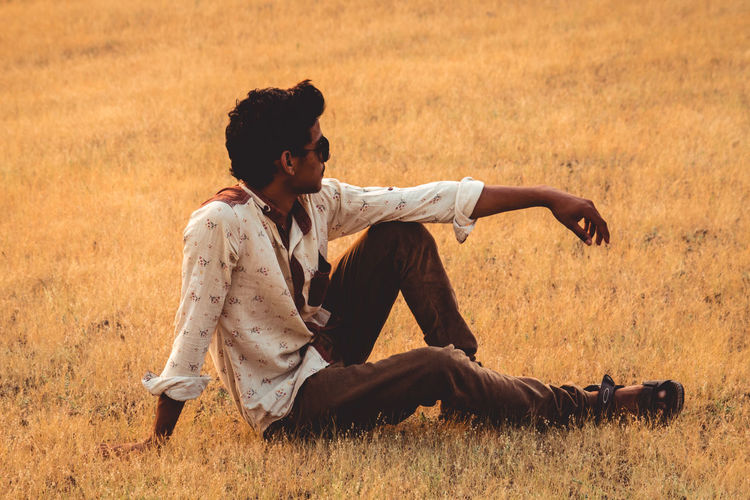 Casual Clothing Contemplation Day Field Full Length Grass Hairstyle Land Leisure Activity Lifestyles Looking Men Nature One Person Outdoors Plant Real People Sitting Sunlight Young Adult Young Men