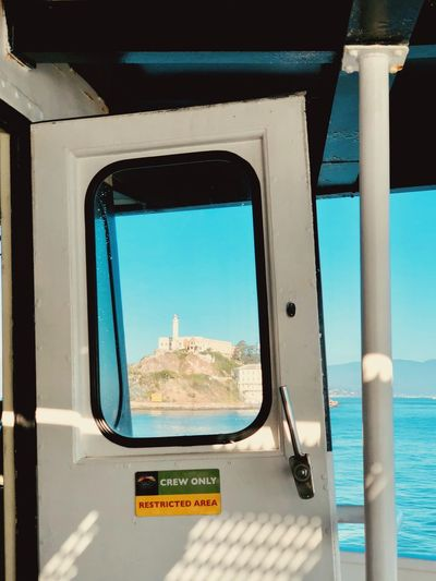 Alcatraz Alcatraz Alcatraz In Sight Alcatraz Island EyeEm Selects Transportation Window Sea Mode Of Transportation Water Day Sky Transparent Travel Sunlight Outdoors Glass - Material Vehicle Interior No People Nature Blue Architecture Text Transportation Motion Travel Shipping  Architecture Nature Freight Transportation Business