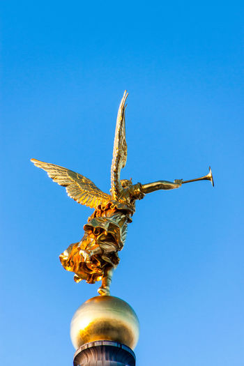 Low angle view of angel statue against blue sky