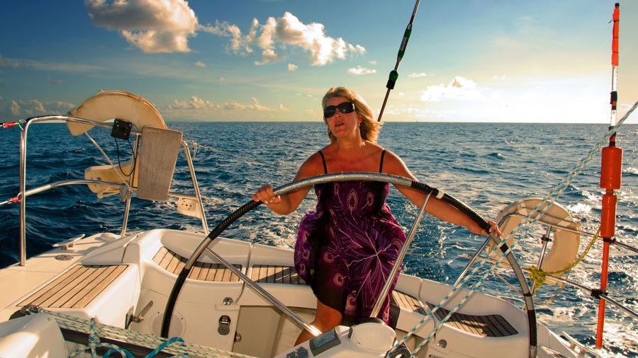 Happy Woman Steering Yacht Against Sky