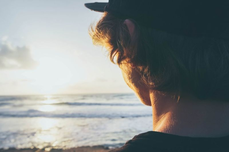 Rear view of young man at beach during sunset