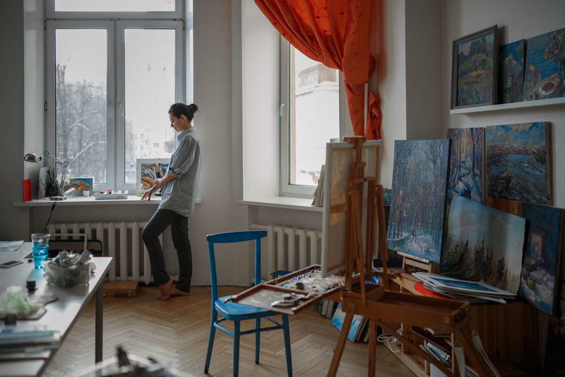 A young brunette woman artist in her art studio near window. Near her easel, paintings and various art equipment. Selective focus. One Person Indoors  Table Furniture Window Standing Mid Adult Real People Side View Home Interior Adult Lifestyles Chair Domestic Room Day Working Hairstyle Messy Artisan Artist Art Art Studio Painting Leisure Activity Hobbies