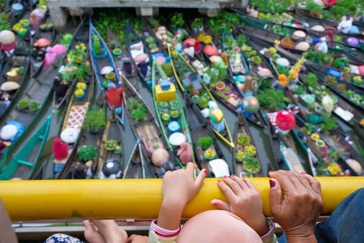 High angle view of people by railing against floating market