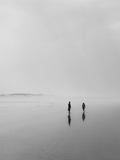 Mid distance view of man and woman at beach during foggy weather