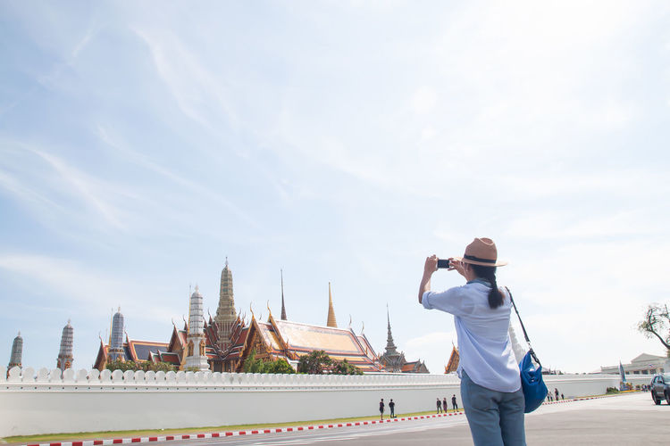Woman using mobile phones to take photo of tourist destinations in Thailand. Traveling concept, travel, tourist, map, holiday, summer, woman, lifestyle, vacation, adventure, outdoor, asian, landmark, activity, traveling, map sing, freedom, smart phone, technology, using mobile, using, city Summer Sky One Person Real People Architecture Photographing Built Structure Photography Themes Standing Building Exterior Lifestyles Leisure Activity Three Quarter Length Nature City Technology Day Cloud - Sky Rear View Holding Wireless Technology Outdoors Cityscape Travel Selfie Camera Taking  Tower Digital Camera Urban Scene