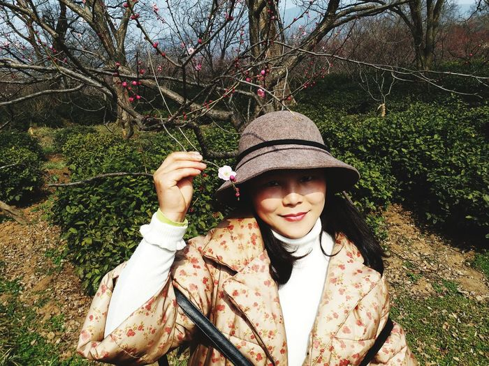 Portrait Of Smiling Woman Holding Blossom On Branch During Sunny Day