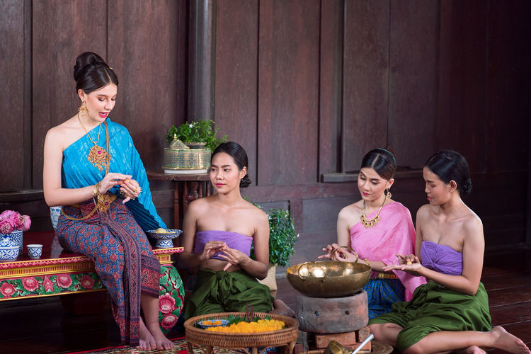 Thai women in ancient costumes in the ayutthaya period in an old house along with thai sweet food