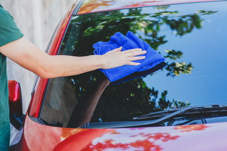 Cropped image of man cleaning red car