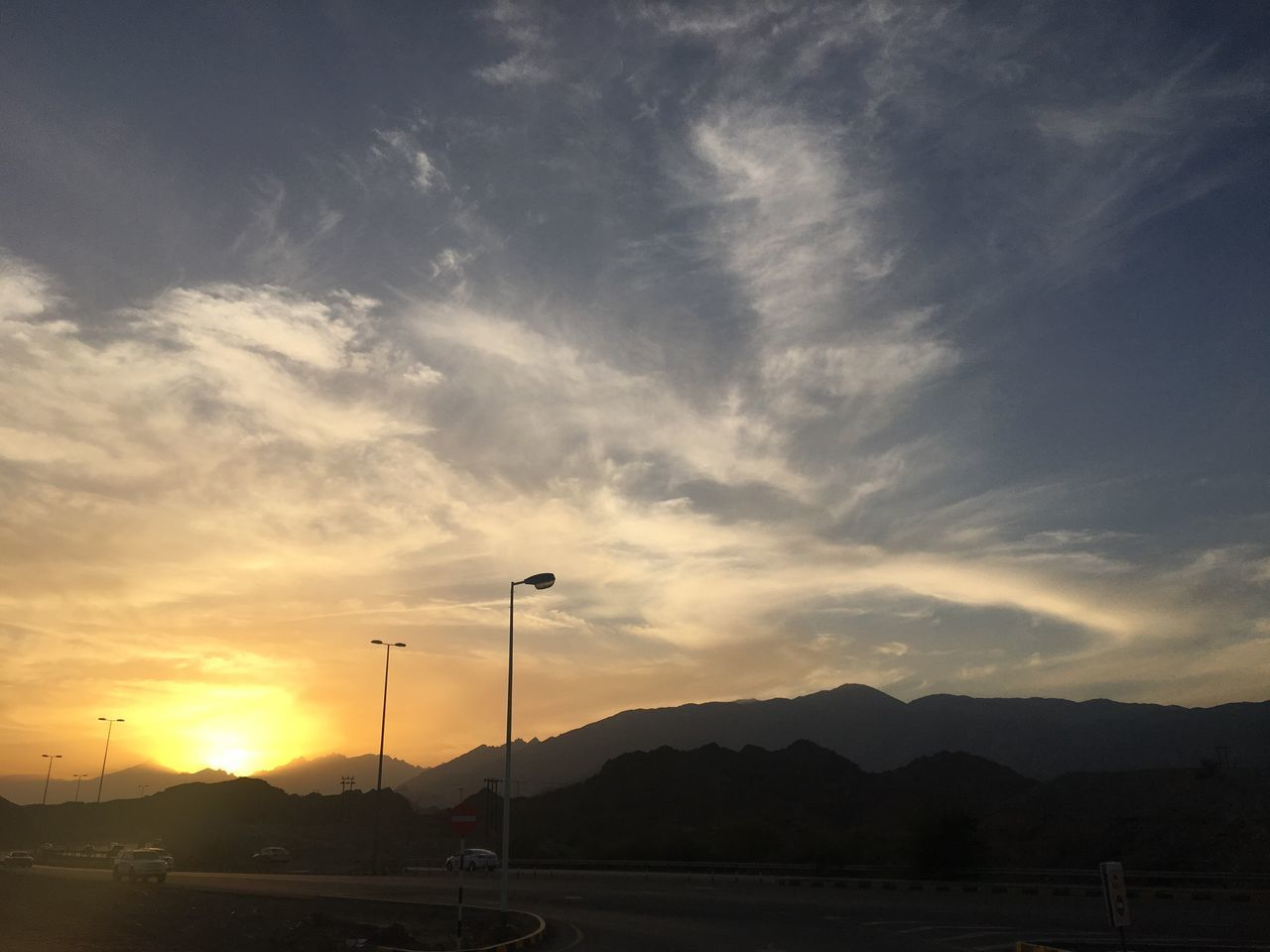 sunset, cloud - sky, car, sky, transportation, silhouette, land vehicle, scenics, nature, sun, street light, beauty in nature, mountain, no people, road, outdoors, day