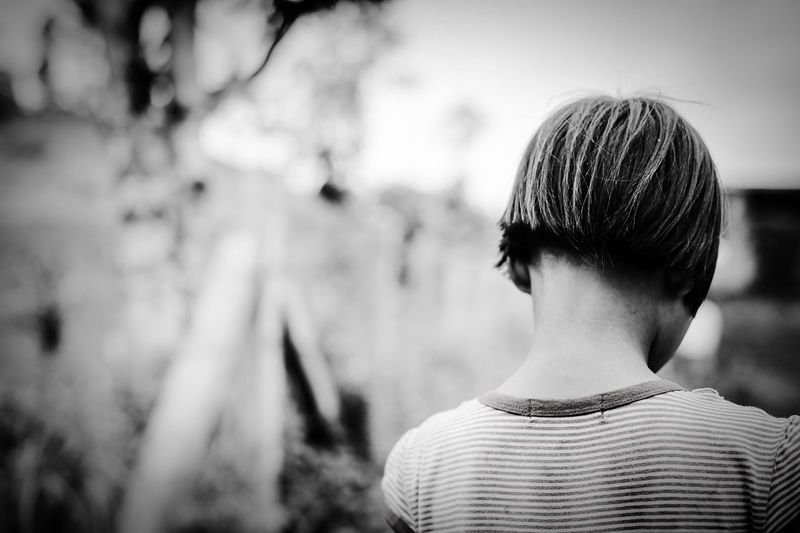 Close-up rear view of girl with short hair at yard