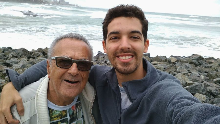 Portrait of young man with grandfather standing on rocky shore