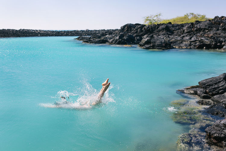 Woman dives into an aqua colored lagoon Water Turquoise Colored Outdoors Blue One Person Rock - Object Sea Lagoon Diving Into Water Dive Swimming Swimmer Isolated Remote Tropical Climate Hawaii Island Splashing Lava Rocks Aquarium Feet Aqua