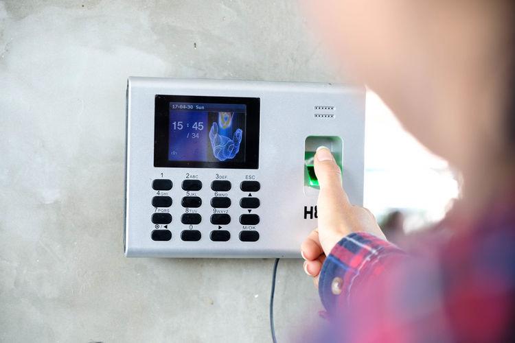 Close-up of woman scanning thumb on intercom