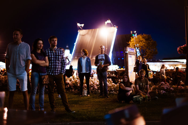 People standing in illuminated park at night