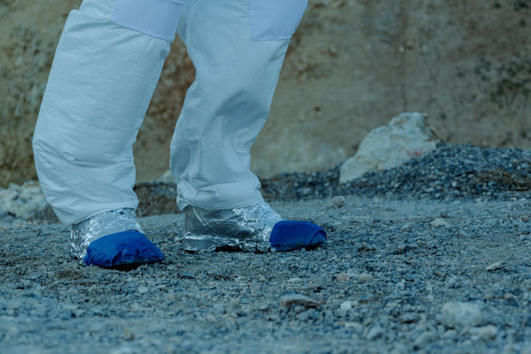 Low section of person in astronaut costume walking on field