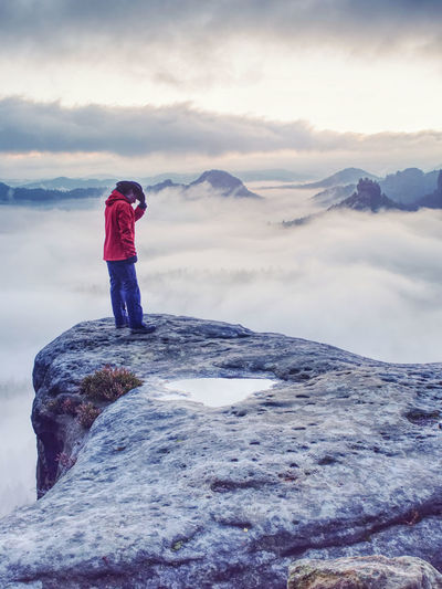 Woman watching sunrise over himalayas, misty mountains national park