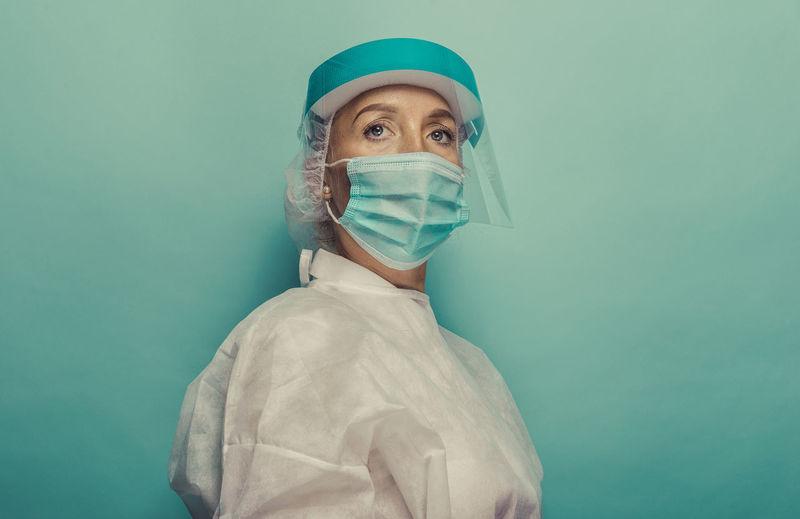 Female doctor wearing mask against blue background