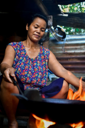 Smiling woman preparing food while sitting by fire