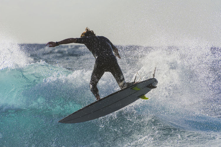 Backward jumper Motion Sport Water Sea One Person Splashing Men Aquatic Sport Real People Lifestyles Nature Adventure Leisure Activity Surfing Day Side View Skill  Power In Nature Outdoors Effort Surfer Watersports Extreme Sports Sportsman Sports Surfboard