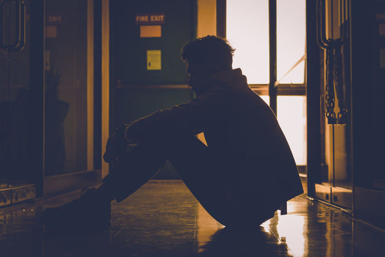 Side view of silhouette young man sitting on floor in corridor