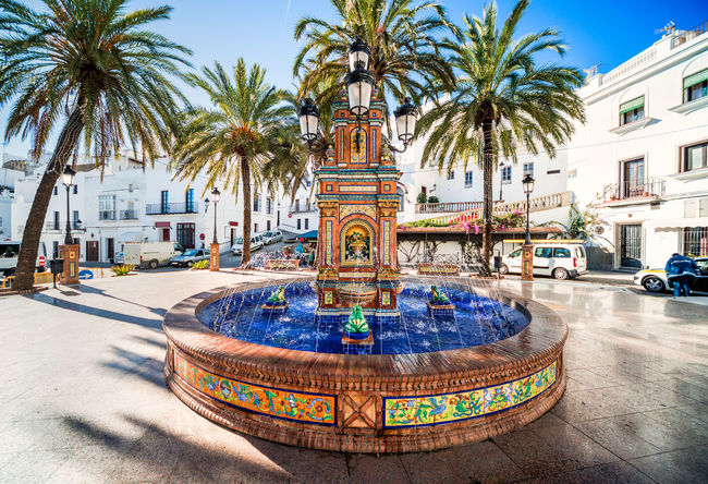 The main square in Vejer de la Frontera is Plaza de Espana, featuring a beautiful fountain with colorful ceramic tiles. Andaulcia Architecture City Colorful Costa De La Luz Cádiz, Spain Flowing Water Fountain History Landmark Outdoors Palm Tree Picturesque Village Plaza De España Sculpture SPAIN Splashing Water Square Sunny Day Town Town Square Travel Destinations Vejer De La Frontera  Village Whitewashed