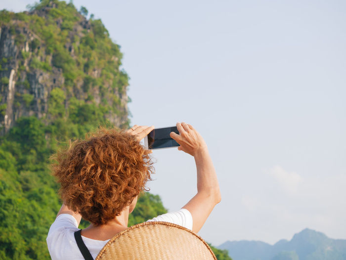 Rear view of woman photographing against sky