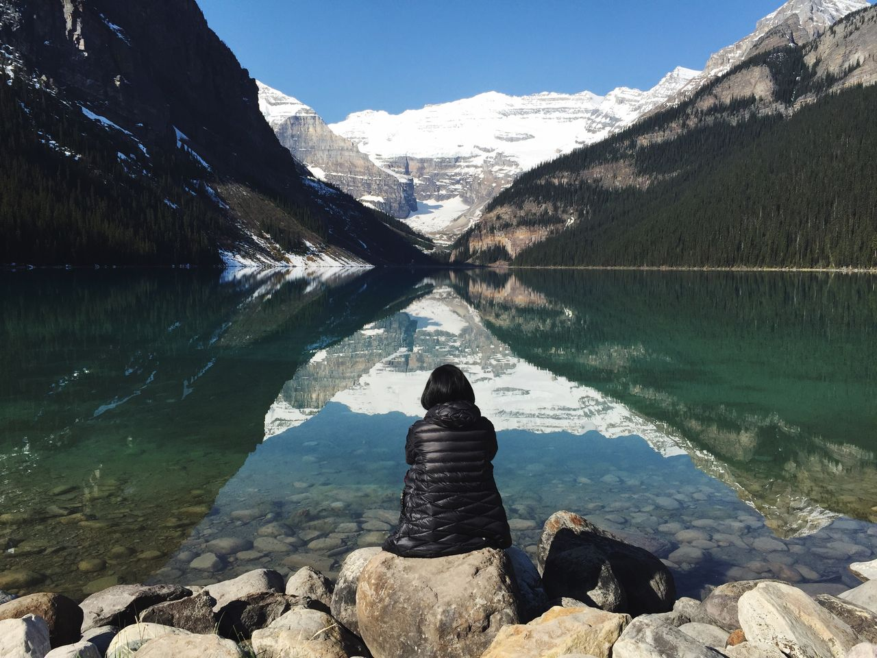 Rear view of woman sitting on rock against calm moraine lake at banff national park