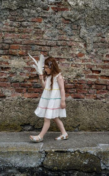 Full length of girl walking while holding feathers on footpath against wall