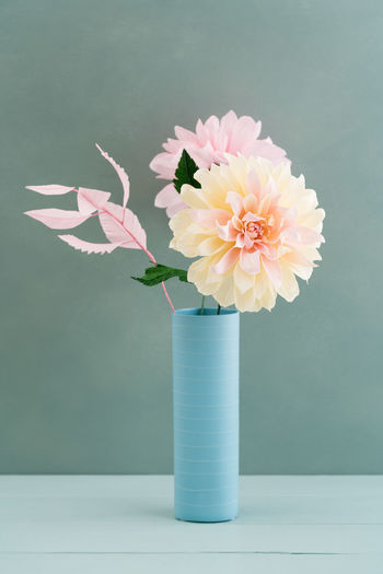 Close-up of flower vase on table against wall