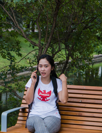 Phone call Bench Casual Clothing Day Front View Leisure Activity Lifestyles Looking At Camera One Person Outdoors Plant Portrait Real People Seat Sitting Three Quarter Length Tree Women Young Adult Young Women