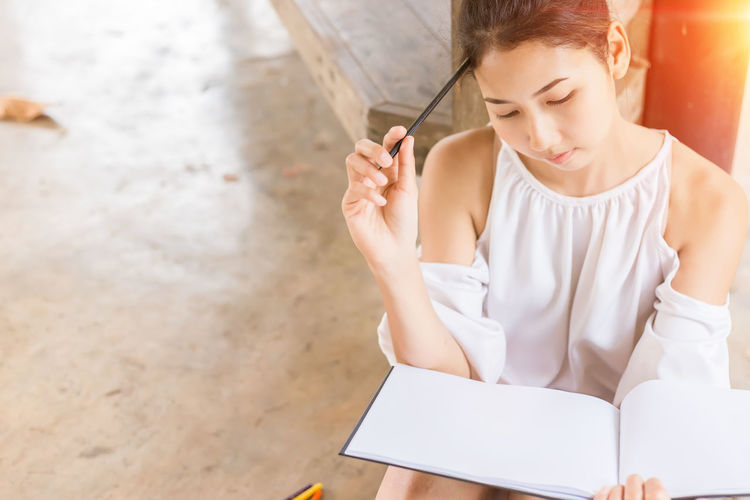 High Angle View Of Woman Studying At Home