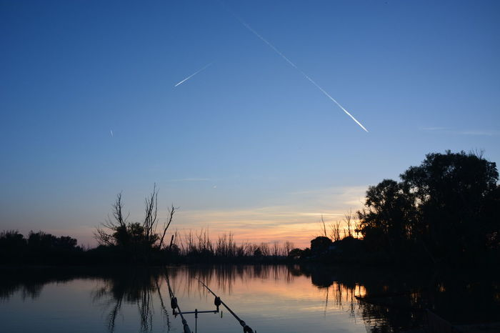 Airplane Astronomy Blue Fishing Rods Fishing Time Horizontal Landscape Nature No People Outdoors Sky Sunset Tree Vapor Trails Water