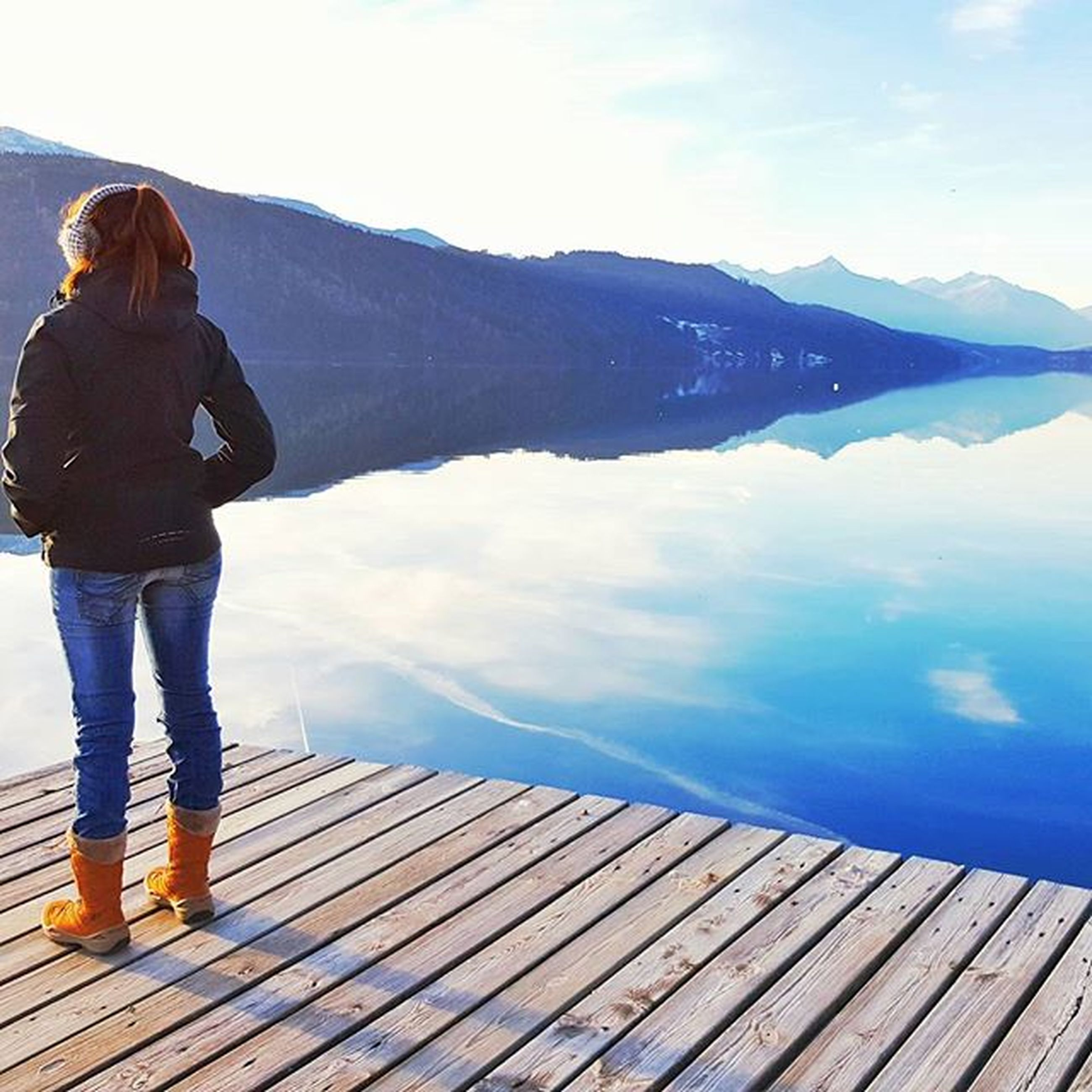 lifestyles, standing, mountain, sky, leisure activity, full length, rear view, water, railing, tranquility, scenics, tranquil scene, casual clothing, looking at view, beauty in nature, nature, pier, men