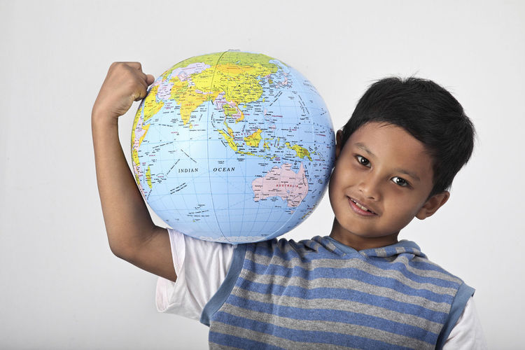 Portrait of smiling boy holding globe against white background