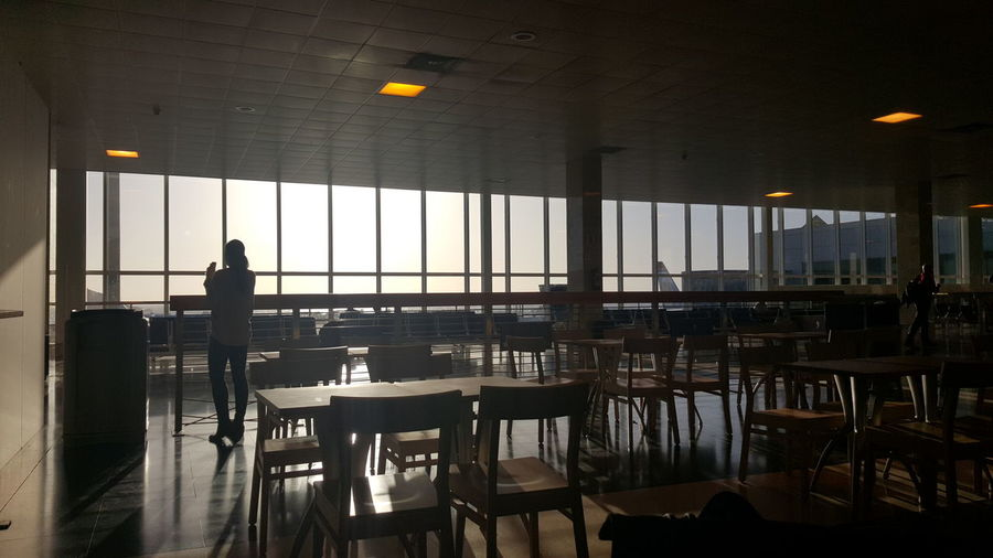 Rear view of woman standing in restaurant at airport