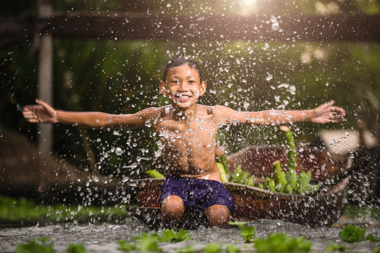 Portrait of happy shirtless boy by splashed water while sitting on boat in river